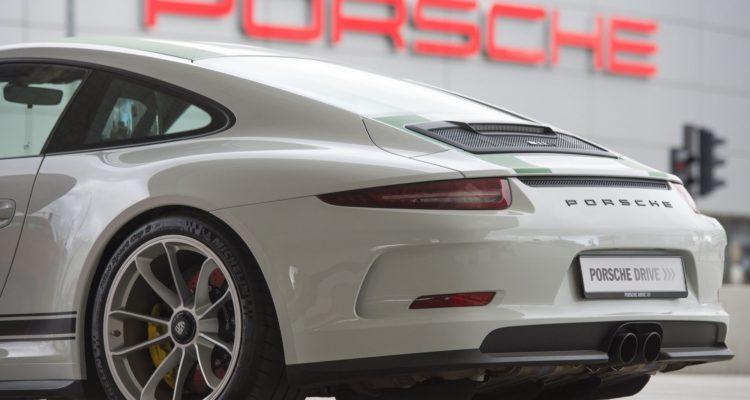 Une Porsche 911 devant le logo de la marque